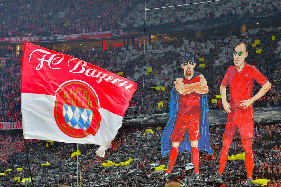 """Franck Ribery als """"Badman"""" (l.) und Arjen Robben als """"Robin"""" als überdimensionale Figuren werden vom Fanblock des FC Bayern München während einer Fan-Choreographie vor Spielbeginn in der Südkurve präsentiert."""