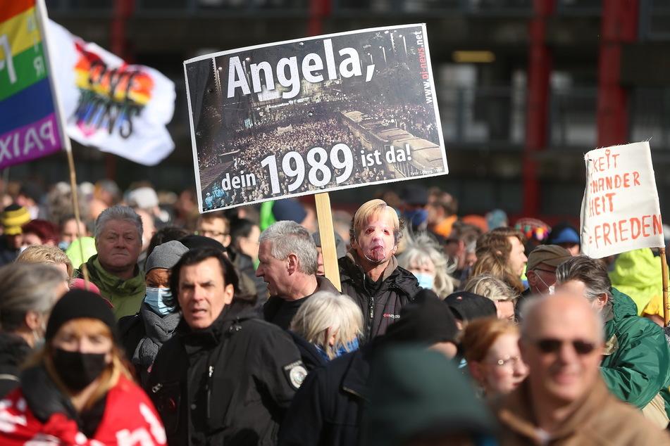 Teilnehmer einer Demonstration protestieren mit Schildern und Fahnen gegen die Corona-Einschränkungen vor dem Düsseldorfer Landtag.