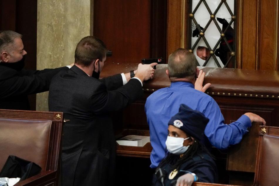 Polizisten mit gezogenen Waffen beobachten, wie Demonstranten versuchen, in die Kammer des Repräsentantenhauses im US-Kapitol einzudringen.