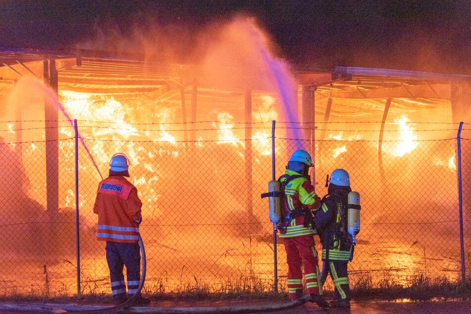 Feuerwehrleute bekämpfen das Flammenmeer in der Lagerhalle.
