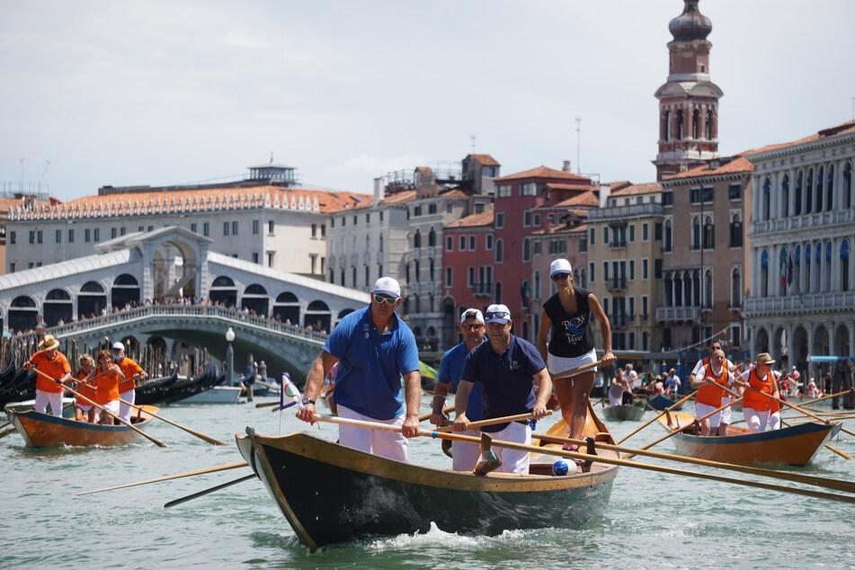 """Menschen nehmen auf Gondeln an der Regatta """"Vogada della Rinascita"""" in Venedig teil. Die Regatta wurde zur Ehrung des medizinischen Personals veranstaltetet, um ihnen für die harte Arbeit während der Corona-Pandemie zu danken. Die Angst vor einer weiteren Infektions-Welle ist groß."""