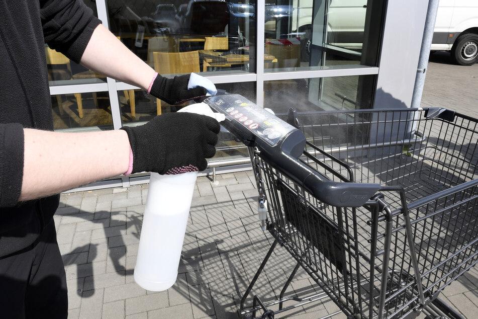 Ein Edeka-Mitarbeiter desinfiziert vor einem Geschäft die Handläufe von Einkaufswagen.