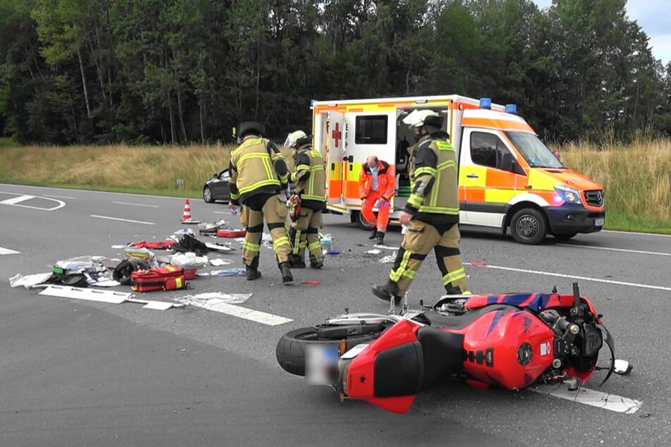 Rettungskräfte arbeiten an der Unfallstelle. Das Motorrad des Verstorbenen liegt auf der Fahrbahn.