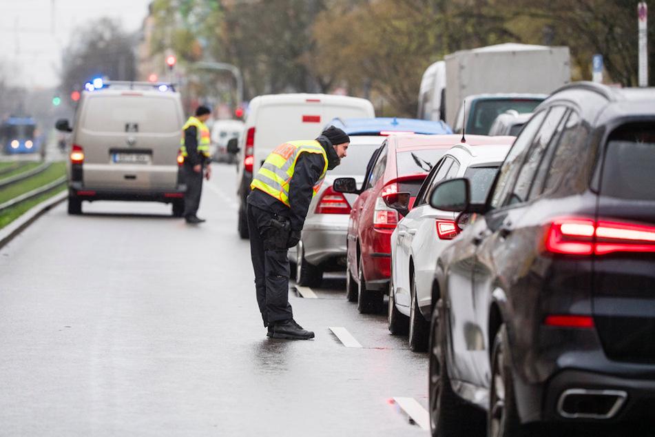 Ein Polizist befragt an einer Kontrollstelle den Fahrer eines Autos in München.