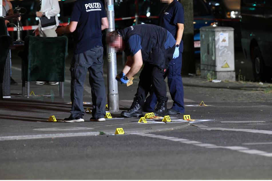 Ein Polizist stellt vor dem Lokal in Berlin-Wedding Patronenhülsen sicher.