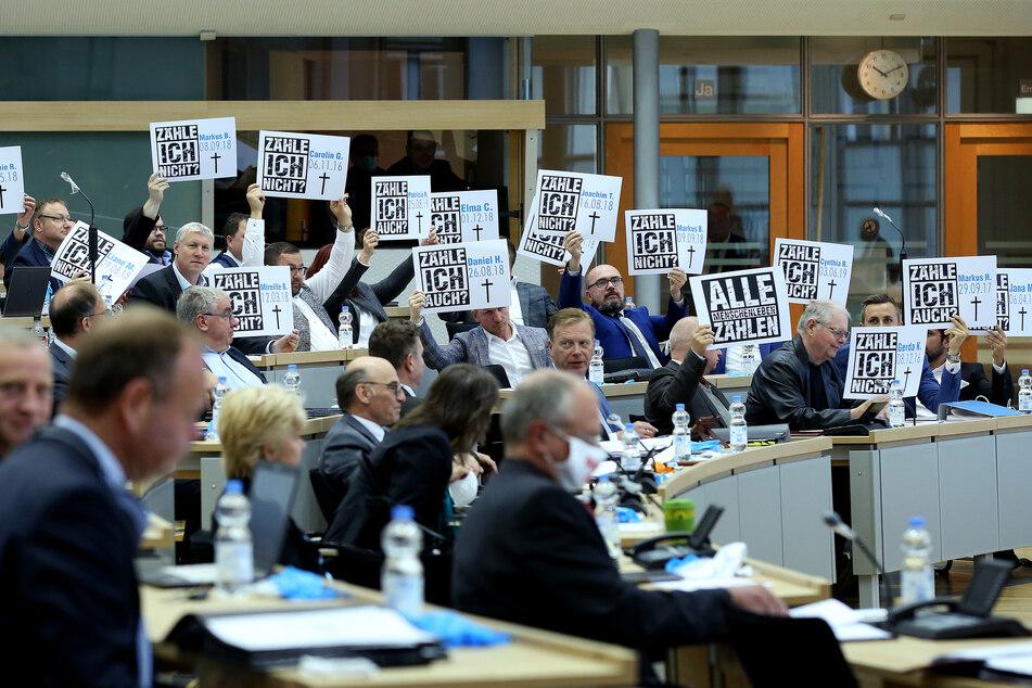Abgeordnete der AfD-Fraktion halten zu Beginn der Landtagssitzung Schilder in die Höhe.