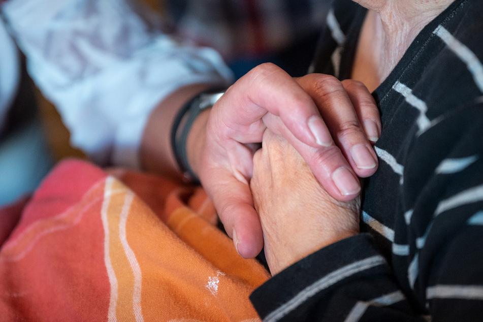 Die Leiterin eines ambulanten Dienstes drückt einer an Demenz und Parkinson erkrankten Patientin die Hand.
