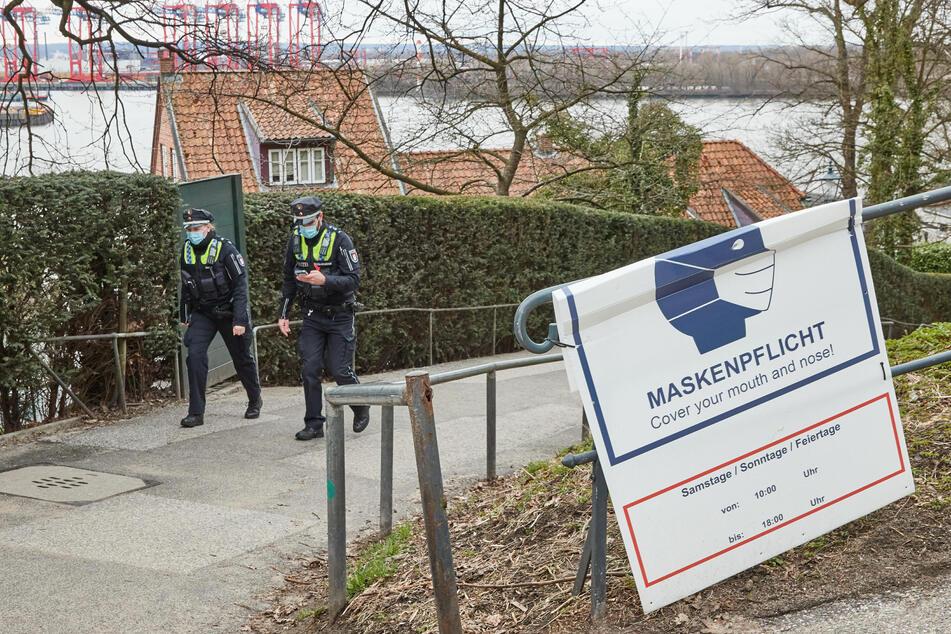 Eine Polizistin und ein Polizist patrollieren am Samstag am Schulberg in Hamburg-Övelgönne und kontrollieren die Einhaltung der geltenden Corona-Regeln.