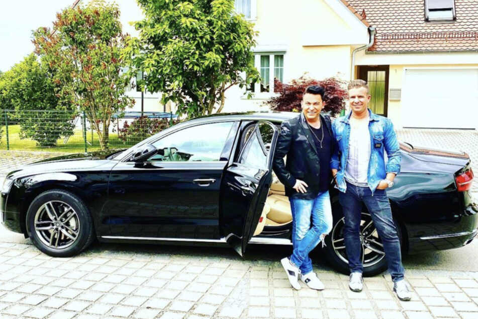 Matthias und sein Bodyguard stehen vor einer Limousine.