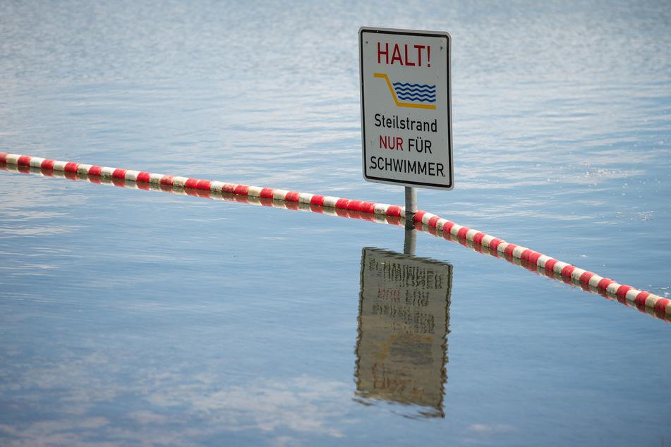 """Ein Schild mit der Aufschrift """"Halt Steilstrand nur für Schwimmer"""" steckt in einem See. (Symbolbild)"""