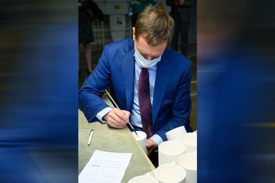 MP Michael Kretschmer (46, CDU) versucht, die berühmten blauen Schwerter auf den Kaffeebecher zu pinseln.
