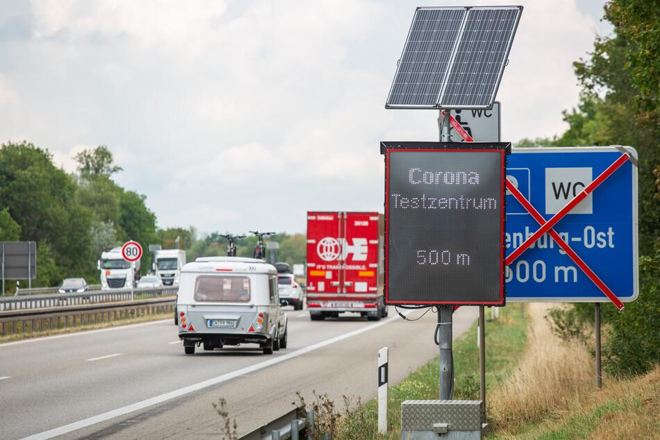 Eine elektronische Anzeigetafel weist an der Autobahn 5 auf die Einfahrt zum Corona-Testzentrum hin.