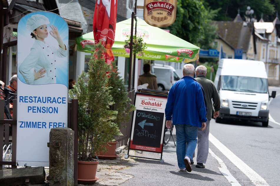 Passanten gehen auf einer Straße nahe der deutsch/tschechischen Grenze an einem Restaurant vorbei.