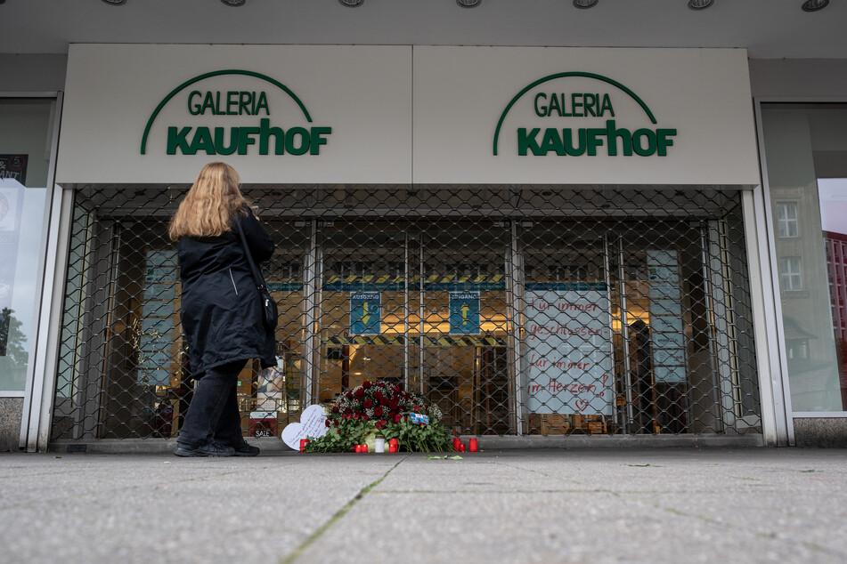 Ein Blumenkranz und Kerzen sind vor der verschlossenen Tür einer Galeria Kaufhof Filiale niedergelegt worden.