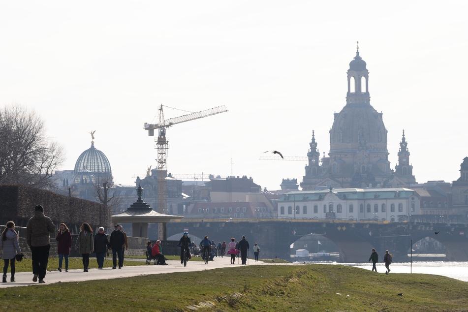 Passanten gehen am Ufer Elbe vor der Kulisse der Altstadt mit der Frauenkirche entlang.