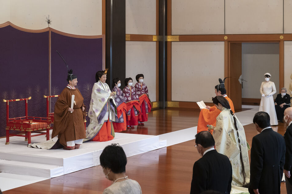 Japans Kronprinz Akishino (M, orangefarbene Kleidung) nimmt zusammen mit seiner Frau Kronprinzessin Kiko an der Zeremonie teil.