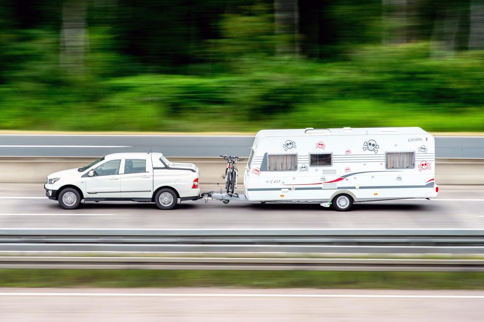 Ein Auto mit angehängtem Wohnwagen ist auf der A7 am Autobahnkreuz Hannover/Kirchhorst in Fahrtrichtung Süden unterwegs.
