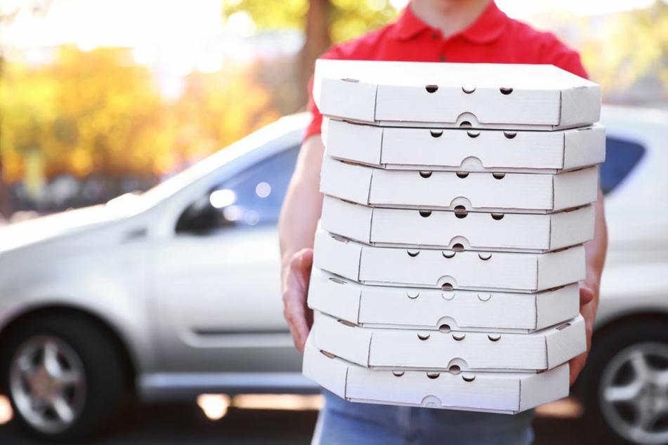 Ein Pizzabote hält mehrere Pizza-Kartons in der Hand (Symbolfoto).