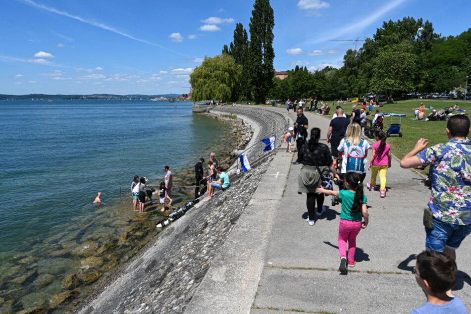 Meersburg: Ausflügler laufen an der Uferpromenade von Meersburg entlang.