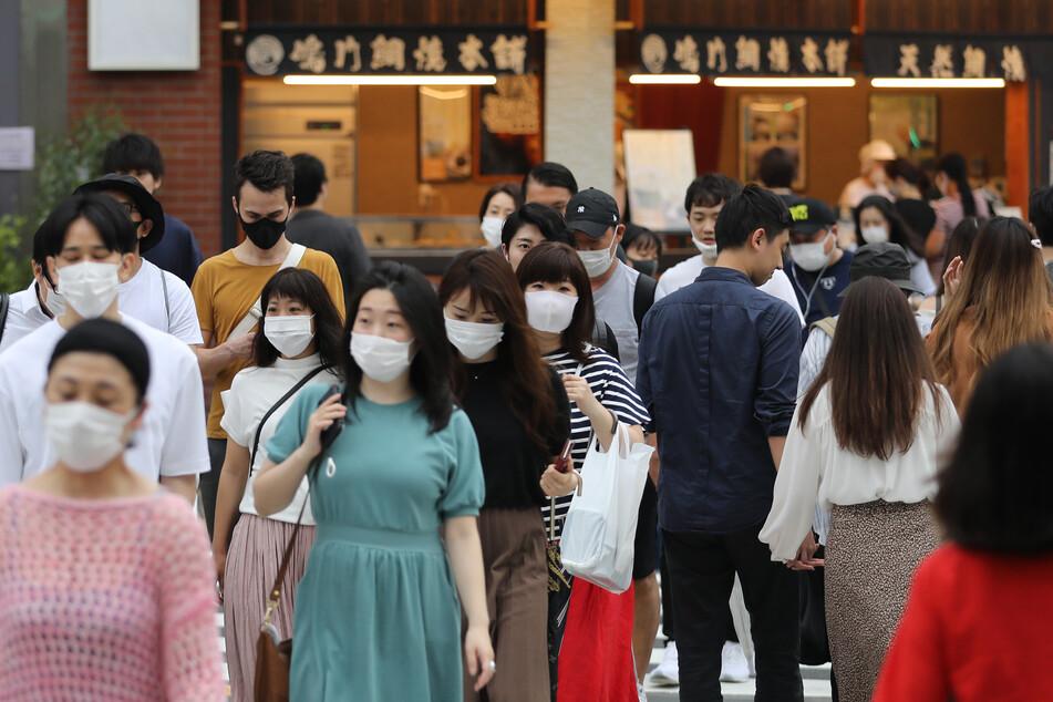 Passanten gehen mit Mundschutz durch eine Straße. Nur wenige Tage nachdem die Stadtregierung von Tokio die Absperrungen aufgrund der Corona-Pandemie aufgehoben hatte, damit Geschäfte wieder öffnen können, bestätigte sie am 14. Juni über 40 neue Fälle von Infektionen mit dem Coronavirus.