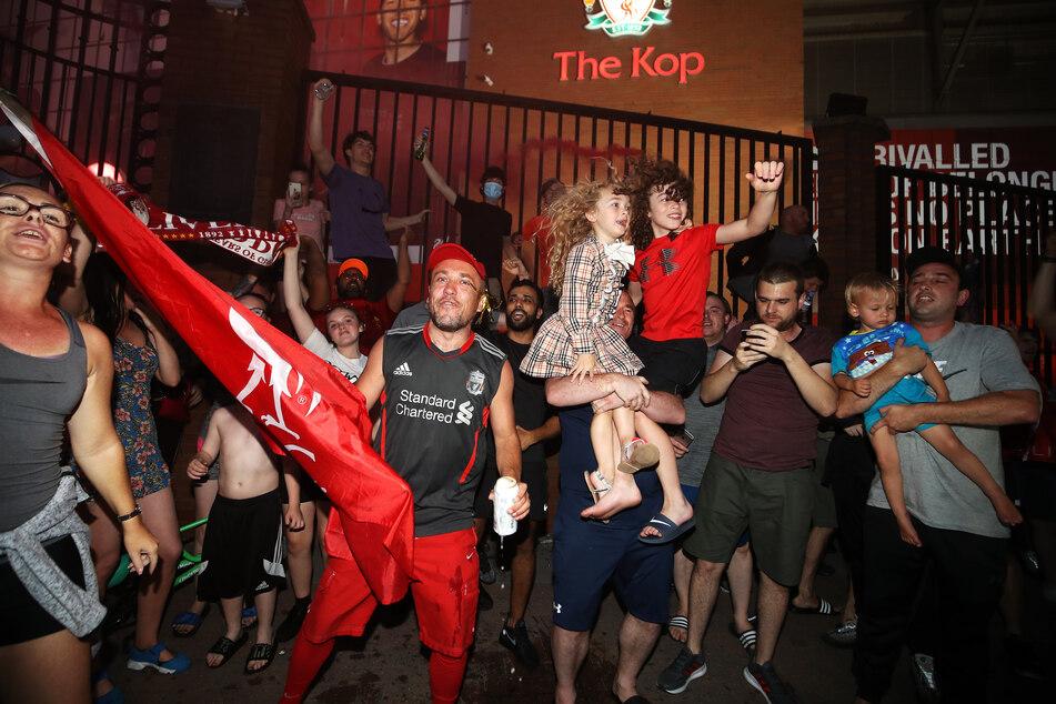 Fans des FC Liverpool feiern vor Anfield, nachdem ihre Mannschaft nach der 1:2-Niederlage von Manchester City gegen Chelsea als Meister der Premier League feststeht.