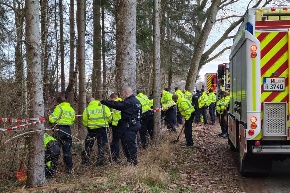 Polizisten durchkämmen das Waldstück, in dem das Erddepot gefunden wurde.
