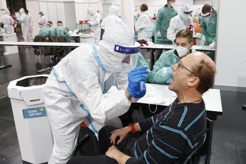 Menschen werden bei Corona-Massentests in der Messehalle in Graz auf das Virus getestet.