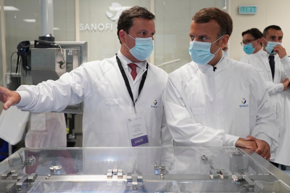 Emmanuel Macron (r.) hört bei einem Besuch einer Fabrik des Pharmaherstellers Sanofi Pasteur Forschern zu.