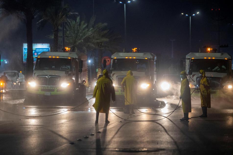 Arbeiter in Schutzanzügen sprühen Desinfektionsmittel auf eine Straße als vorbeugende Maßnahme gegen die Verbreitung des Coronavirus.