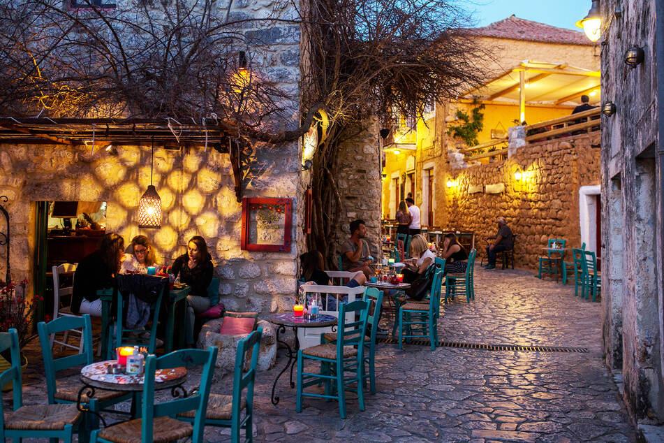 Touristen sitzen in einem Café in Areopoli. Stehen dürfen sie fortan nicht mehr in den Lokalen.
