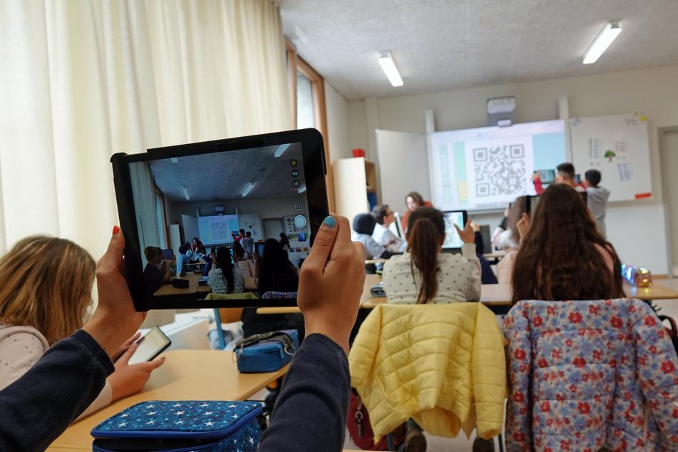 Eine Fünfklässlerin hält ein Tablet hoch, um einen QR-Code zu scannen.