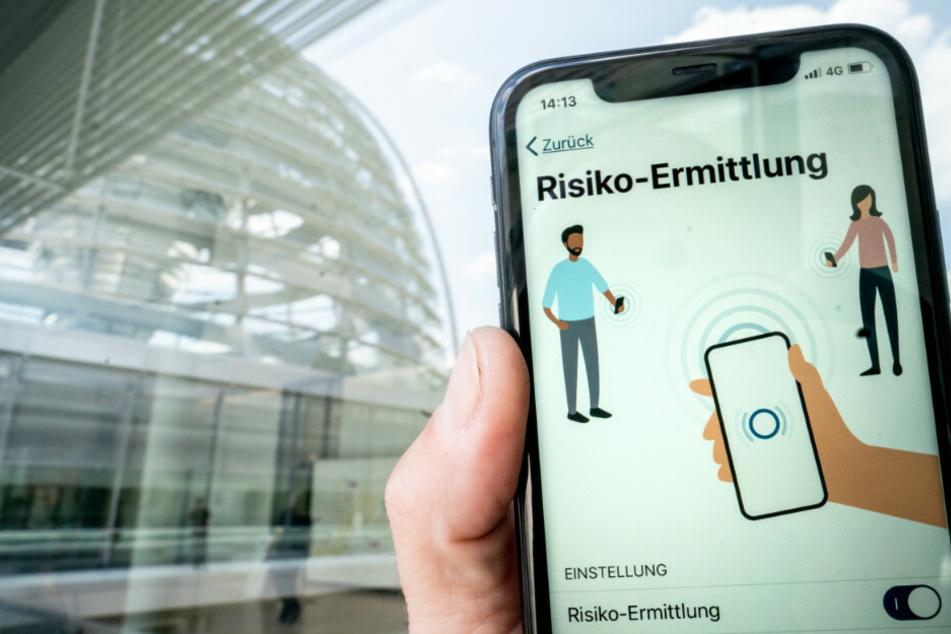 Die Corona-Warn-App mit der Seite zur Risiko-Ermittlung ist im Display eines Smartphone vor der Kuppel des Reichstagsgebäudes zu sehen. Am Montag soll die App um zwei neue Funktionen erweitert werden.