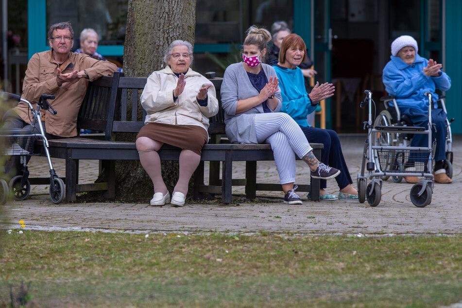 Bewohner und Pflegekräfte applaudieren nach einem kleinen Konzert vor dem AWO Seniorenhaus Schelfwerder, das wegen der Corona-Krise für Besucher gesperrt ist. (Archivbild)