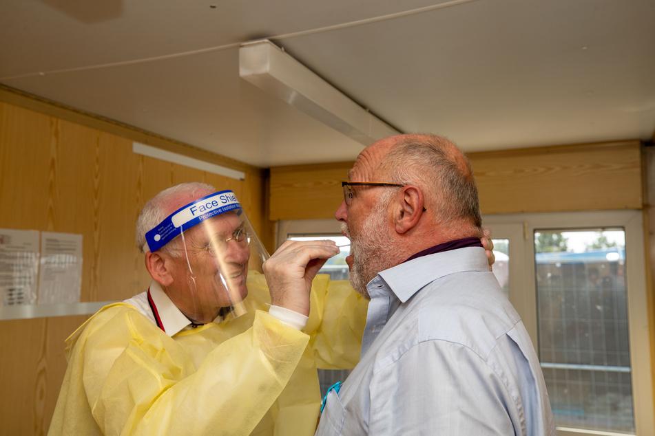 Die Zahl der Infizierten steigt stark an. Im Bild nimmt der Allgemeinarzt Klaus Heckelmann (l) einen Abstrich von einem Mann.