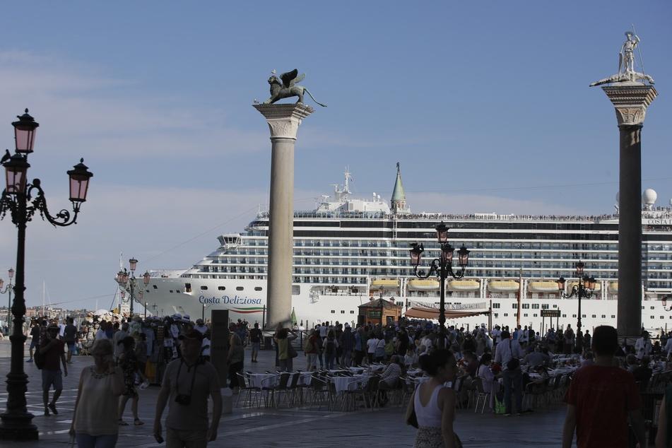 """Das Kreuzfahrtschiff """"Costa Deliziosa"""" fährt am Markusplatz in Venedig vorbei, auf dem zahlreiche Touristen unterwegs sind."""
