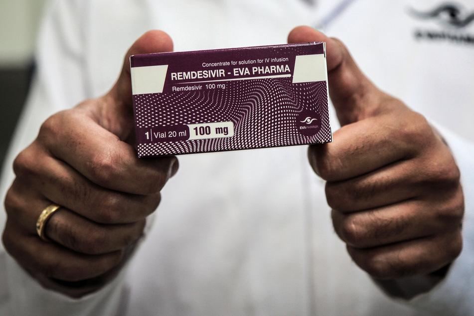 """Ägypten, Gizeh: Ein Mitarbeiter des ägyptischen Pharmaunternehmens """"Eva Pharma"""" hält eine Medikamenten-Verpackung des Wirkstoffs Remdesivir, einem antiviralen Breitspektrum-Medikament."""