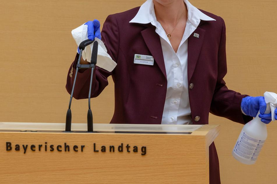 Eine Saaldienerin desinfiziert während der Sitzung des bayerischen Landtags nach jedem Redebeitrag das Rednerpult und wechselt die Schutzüberzüge der Mikrofone.