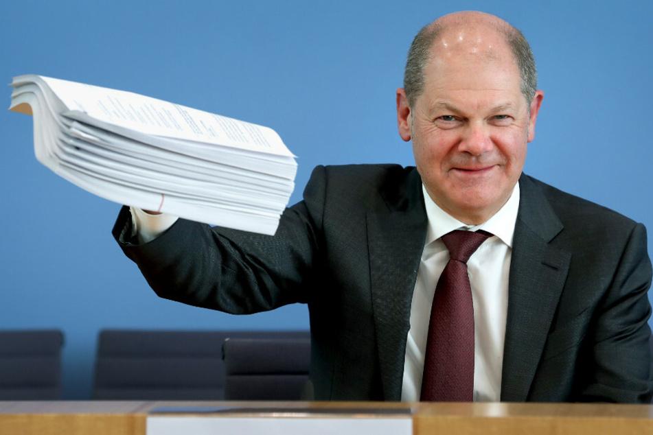 Olaf Scholz (61, SPD), Bundesfinanzminister, gibt eine Pressekonferenz zum Hilfspaket der Bundesregierung für Betroffene der Corona-Krise und hält einen Stapel Unterlagen in die Höhe.