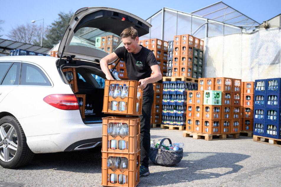 Leere Getränkekisten werden aus einem Auto geladen.