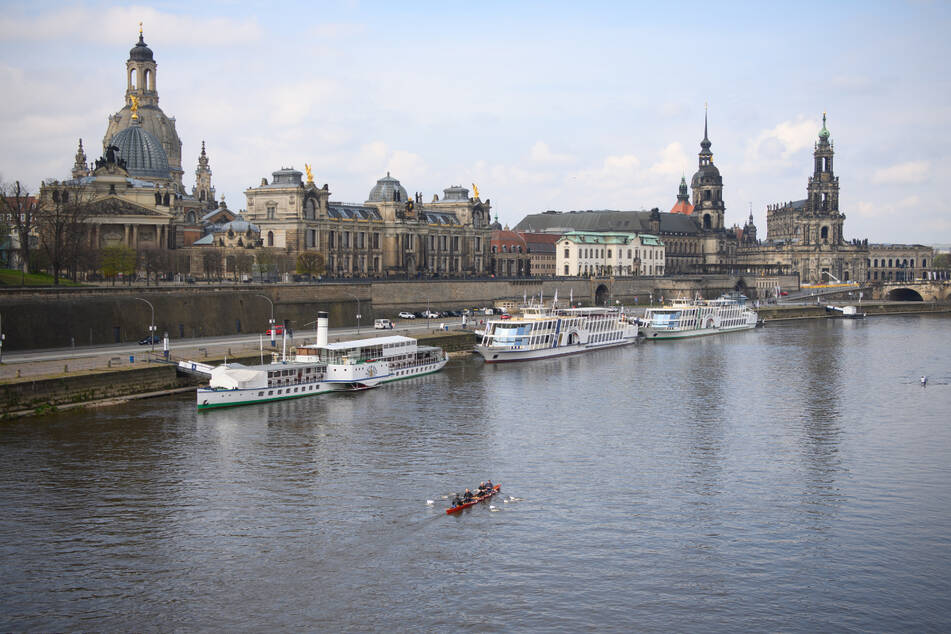 Ein Ruderboot fährt auf der Elbe vor der Altstadt mit der Frauenkirche, der Kunstakademie, der Brühlschen Terrasse, dem Ständehaus, dem Hausmannsturm und der Hofkirche vorbei.
