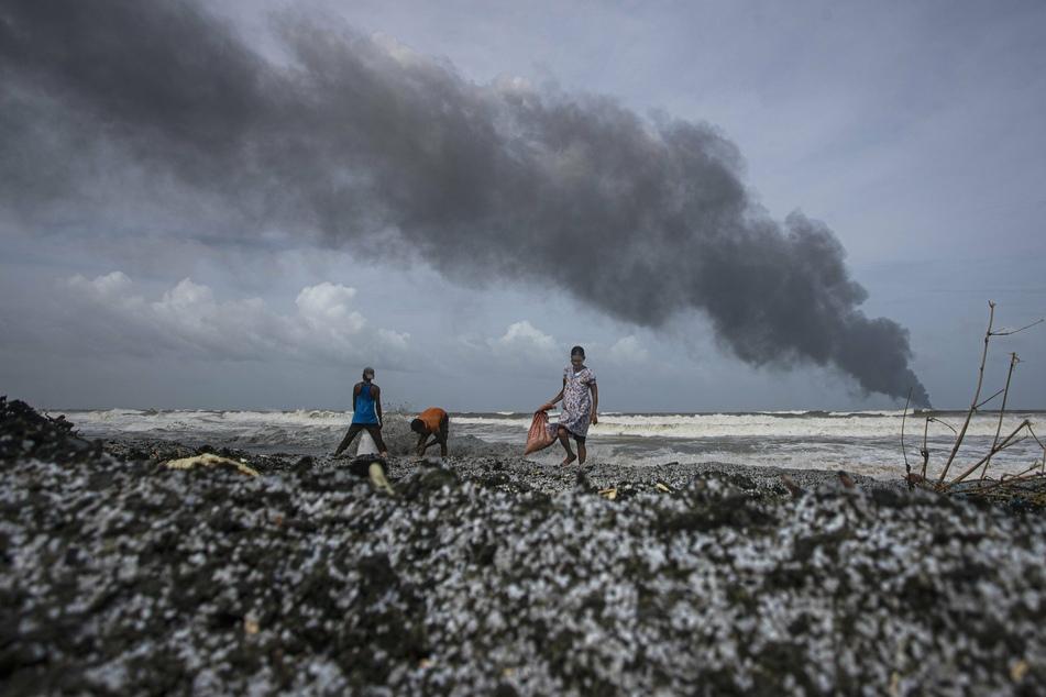 """Menschen gehen über den mit Mikroplastik verschmutzten Strand vor dem Wrack des brennenden Schiffes MV """"X-Press Pearl"""" aus Singapur, das vor dem Hafen von Colombo in Kapungoda, einem Außenbezirk von Colombo, vor Anker liegt."""
