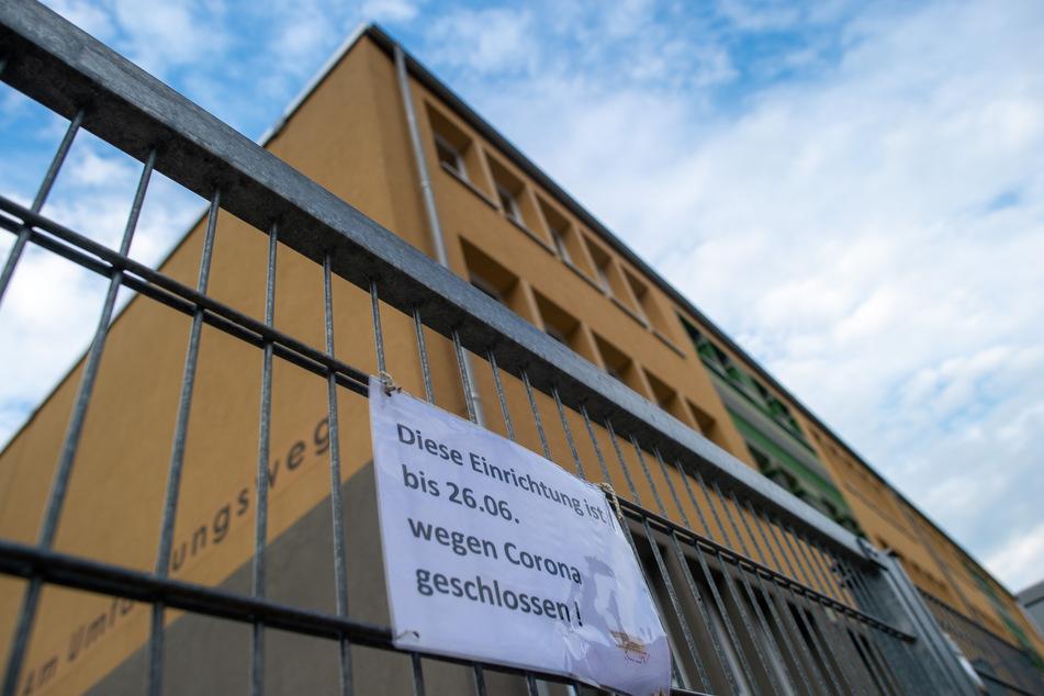 """Ein Schild mit der Aufschrift """"Diese Einrichtung ist bis 26.06. wegen Corona geschlossen!"""" hängt am Eingang zur """"Grundschule am Umfassungsweg""""."""