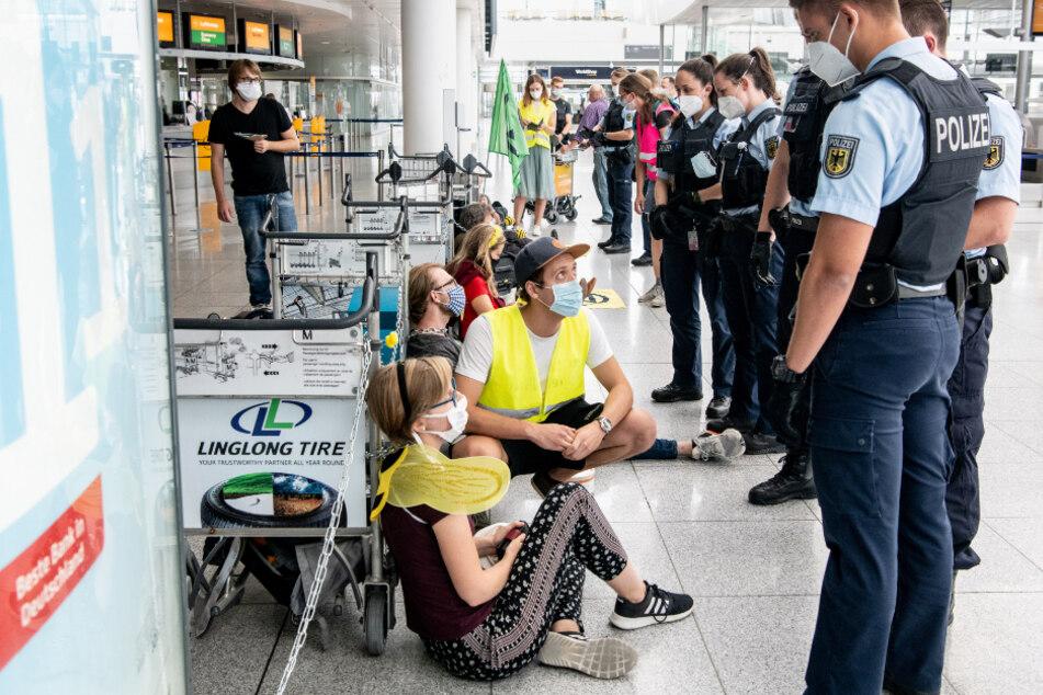 Polizisten unterhalten sich mit den Aktivisten, die sich am Flughafen München mit Gepäckwagen in einem Durchgangsbereich zu den Abfluggates aneinander gekettet haben.