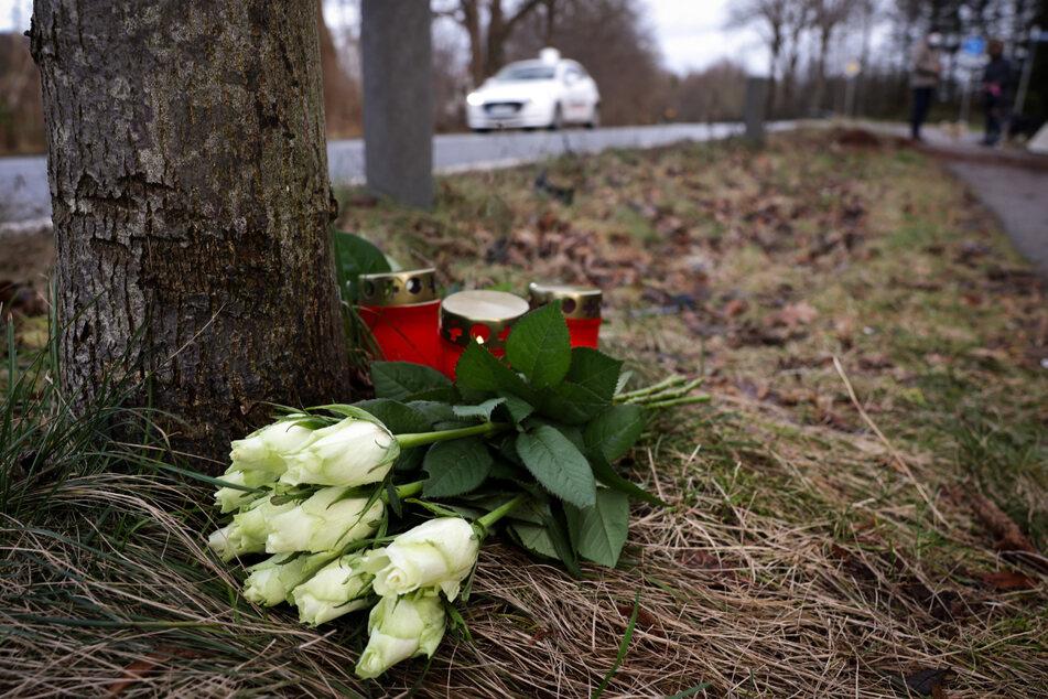 Blumen liegen an der Stelle, wo ein Autofahrer drei Menschen getötet hat.