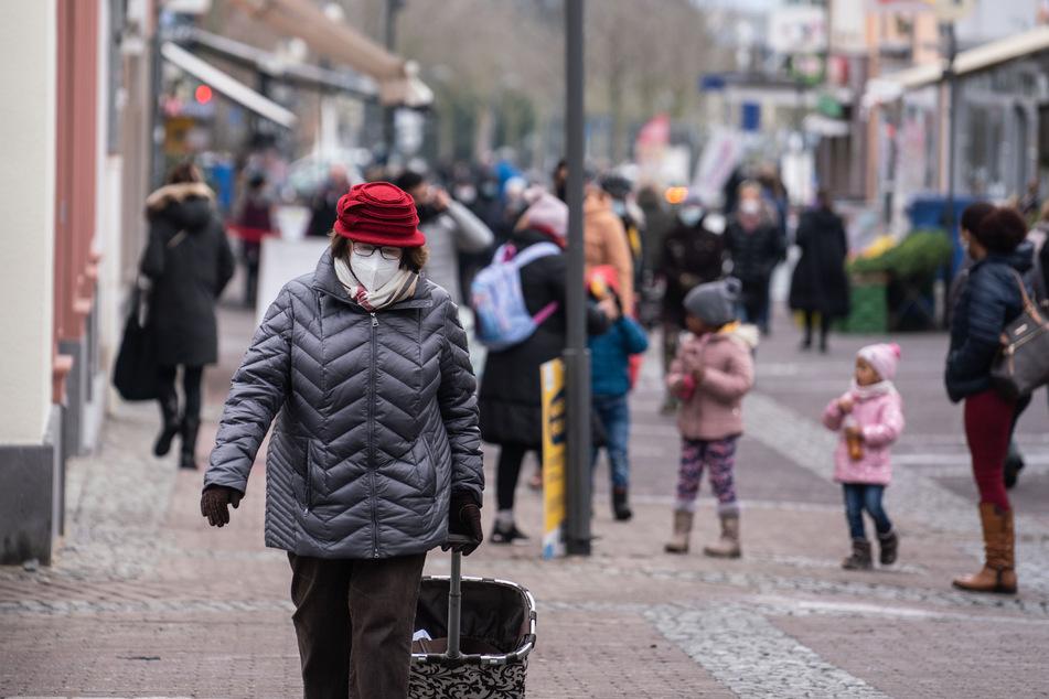 Eine Frau (l) geht mit einer FFP2-Maske geschützt durch die Fußgängerzone der Stadt Oberursel.