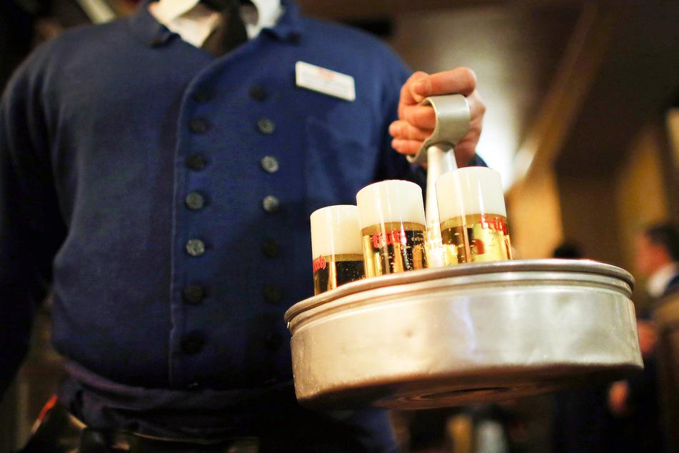 Ein Köbes (Kellner) trägt in einem Kölner Brauhaus Kölsch-Bier.