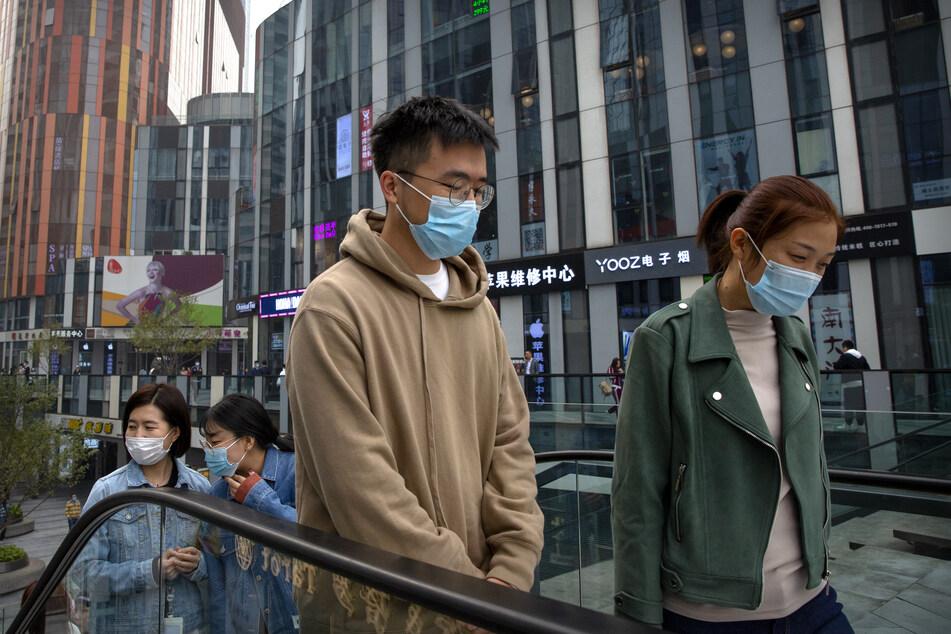 China, Peking: Passanten tragen Nasen-Mund-Bedeckungen während sie in einem Einkaufs- und Bürogebäude auf einer Rolltreppe fahren.