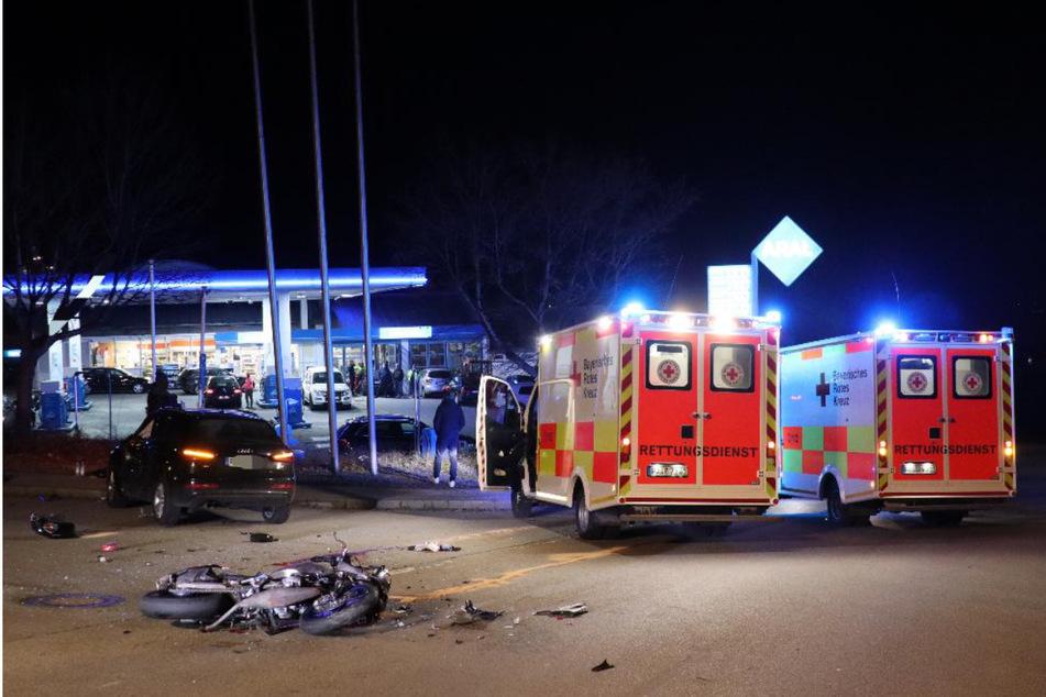 Rettungswagen stehen an der Unfallstelle. Das zerstörte Motorrad liegt im Vordergrund.