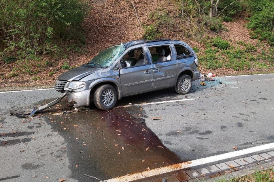 Der Chrysler steht stark beschädigt auf der Straße.