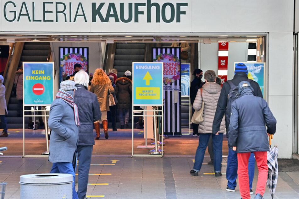 Kunden von Galeria Kaufhof warten am Eingang des Kaufhauses in München auf ihren Einlass.